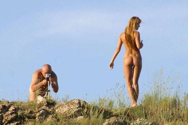 Nagi fotograf robi zdjęcie naturystce na plaży